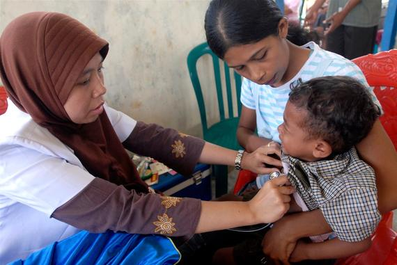 A health care practitioner cares for a mother and child in Indonesia.