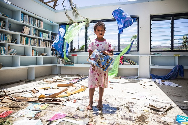 Makelesi, 7, standing in destoryed library of Nabau District School in Ra Province.