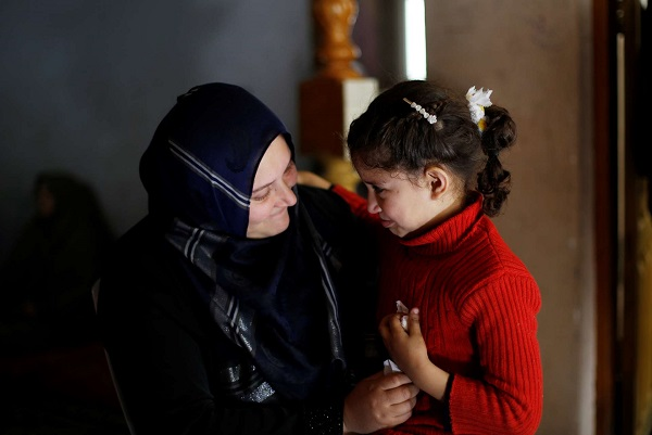 Neveen Barakat comforts her 6 year-old daughter Rosol in Beit Lahia in the northern Gaza Strip.