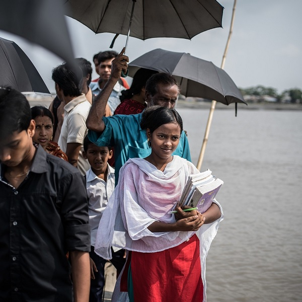 Joya Dhali (carrying books), 17, in southern Bangladesh, refused to get married at age 16.