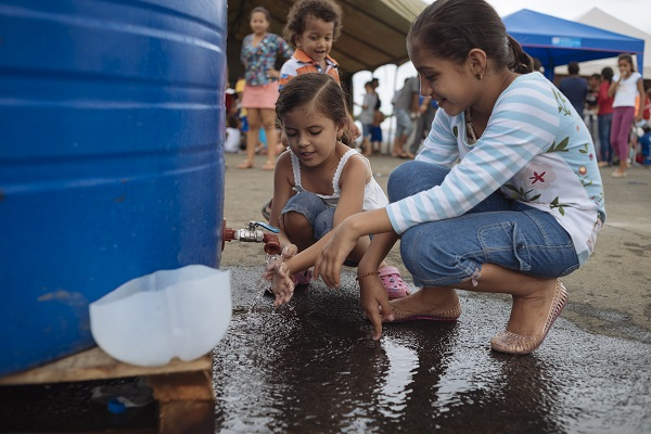Children affected by the Ecuador earthquake wash their hands in the temporary shelter
