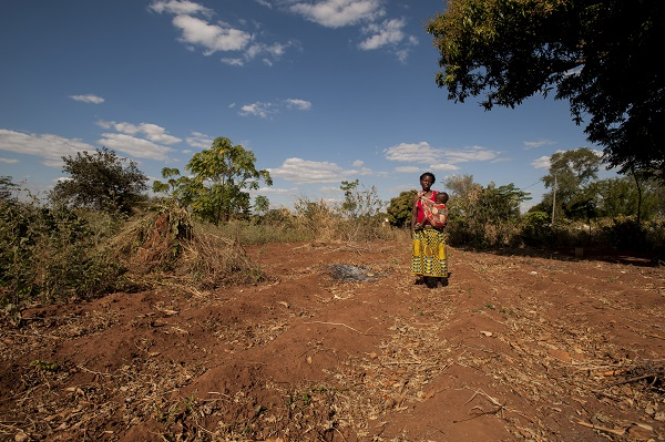 Mother Alinafe and her daughter Desire stand in a barren field in Malawi.