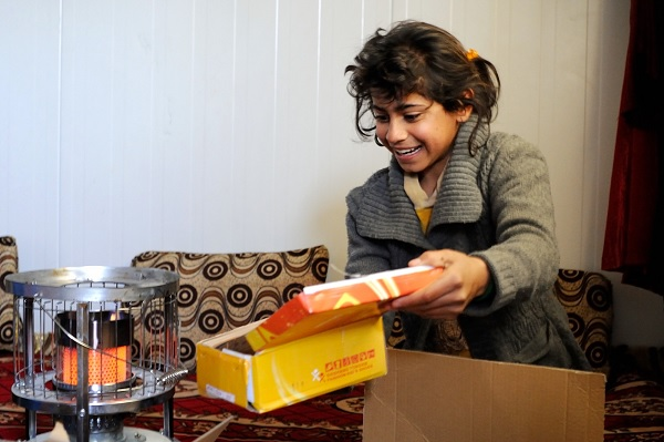 Dunya, 13, displaced in Iraq, opens a box of winter shoes.