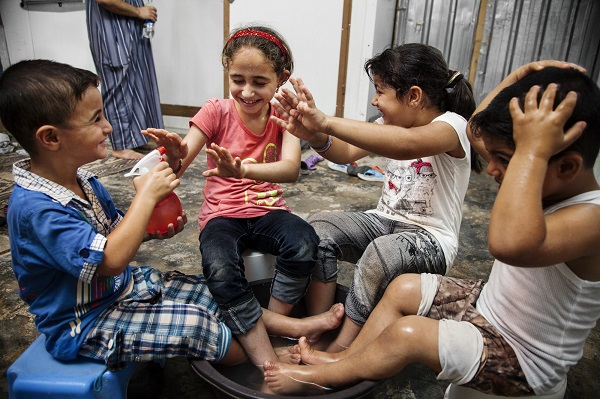 Mohammed, 5 from Syria, sprays water on his sister and cousins in Jordan's Za'atari refugee camp.