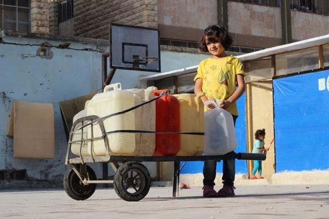 Huda stands next to a cart holding jerry cans filled with water.