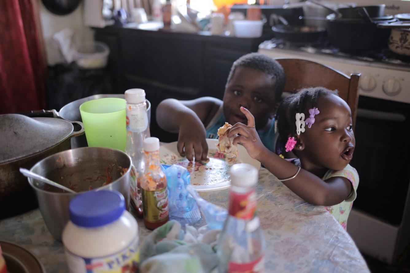 Alishia (right) and her cousin, KJ, eat a snack at their grandmother's home, in Belize City.
