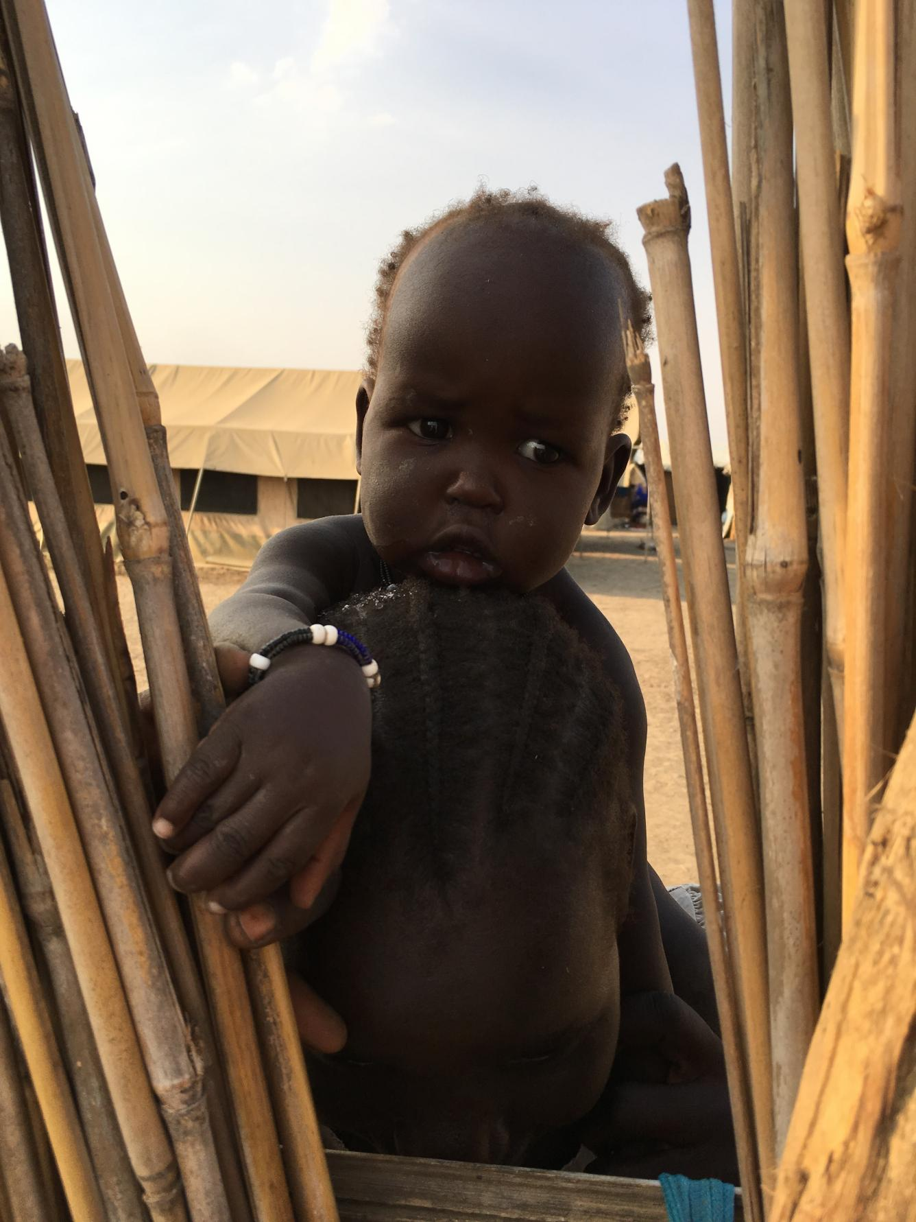 A young child peers through the fence at a UNICEF-supported school in Bentiu.