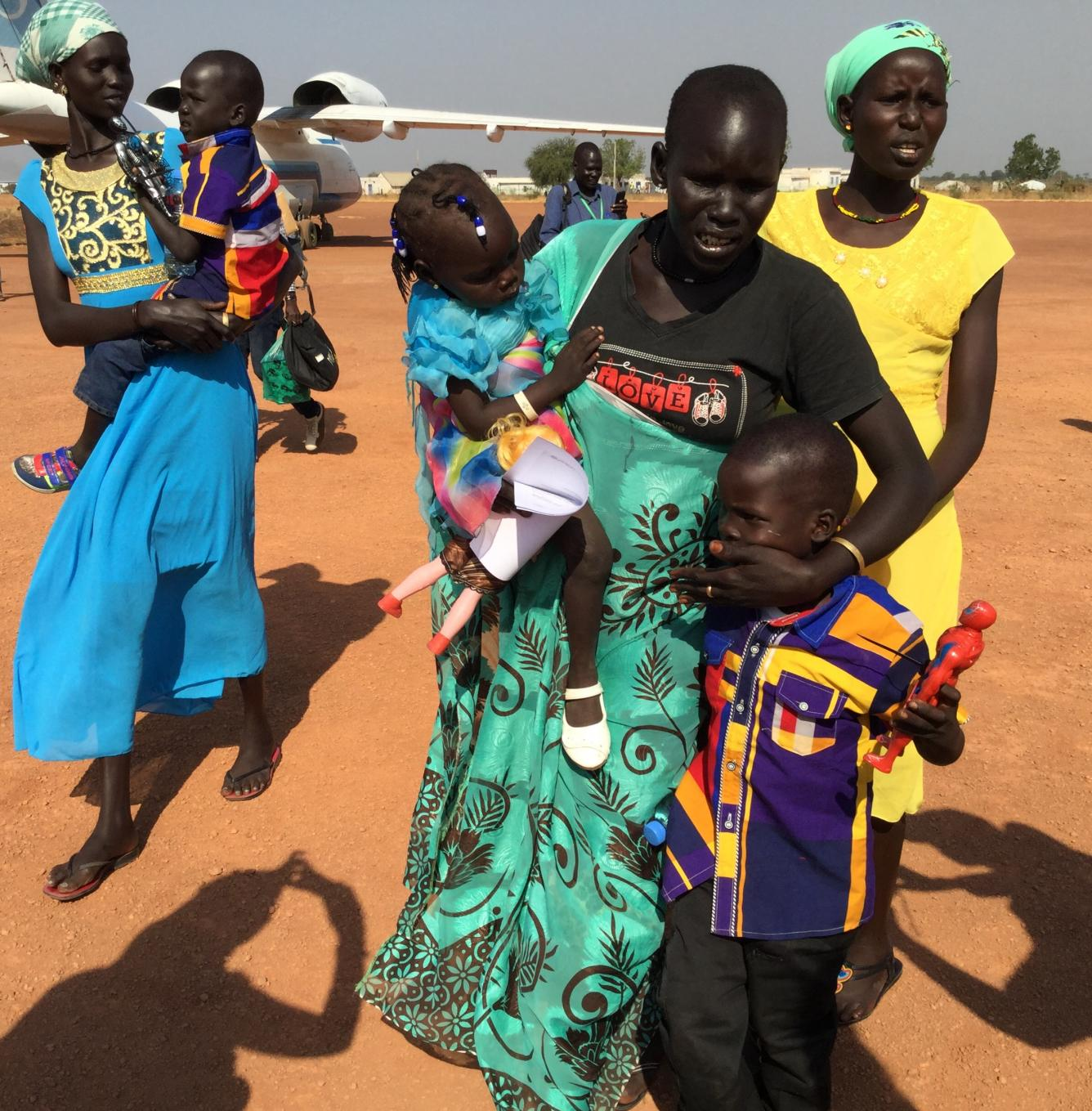 A mother (centre) is overcome with emotion after being reunited with her three children after a two-year separation. UNICEF facilitated the tracing and reunion at the Rubkona air strip in northern S. Sudan.