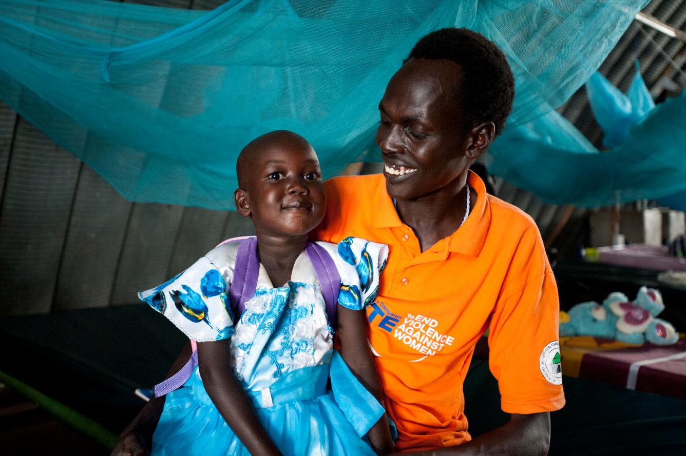 Nyajime sits with her father in a UNICEF-supported health centre