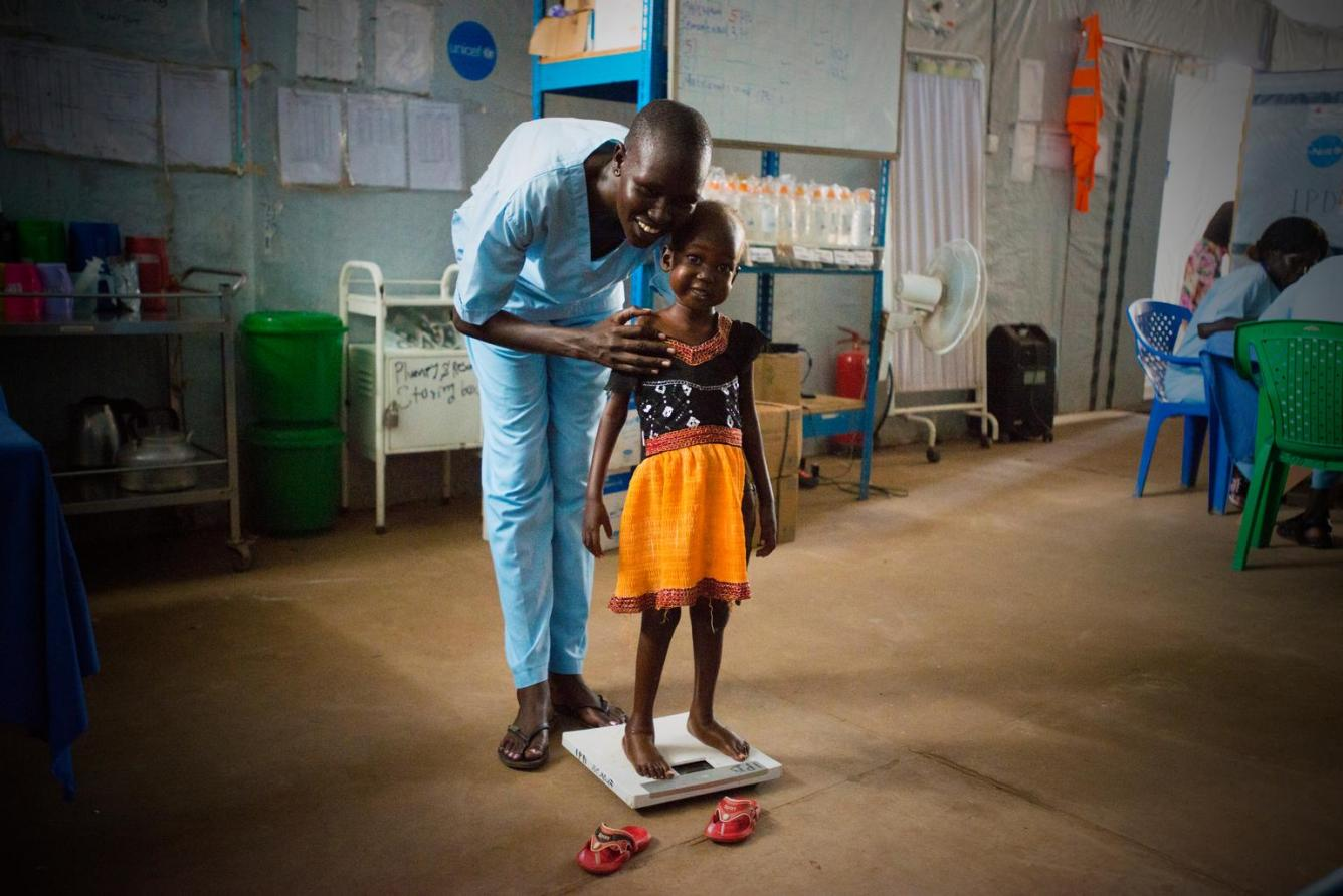 Nyajime is weighed with the help of her father