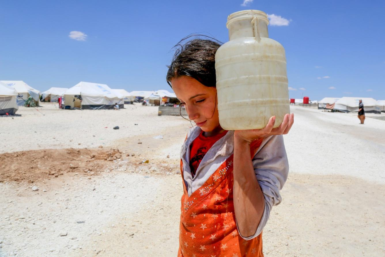 a girl carries water in the Ain Issa refugee camp in Syria