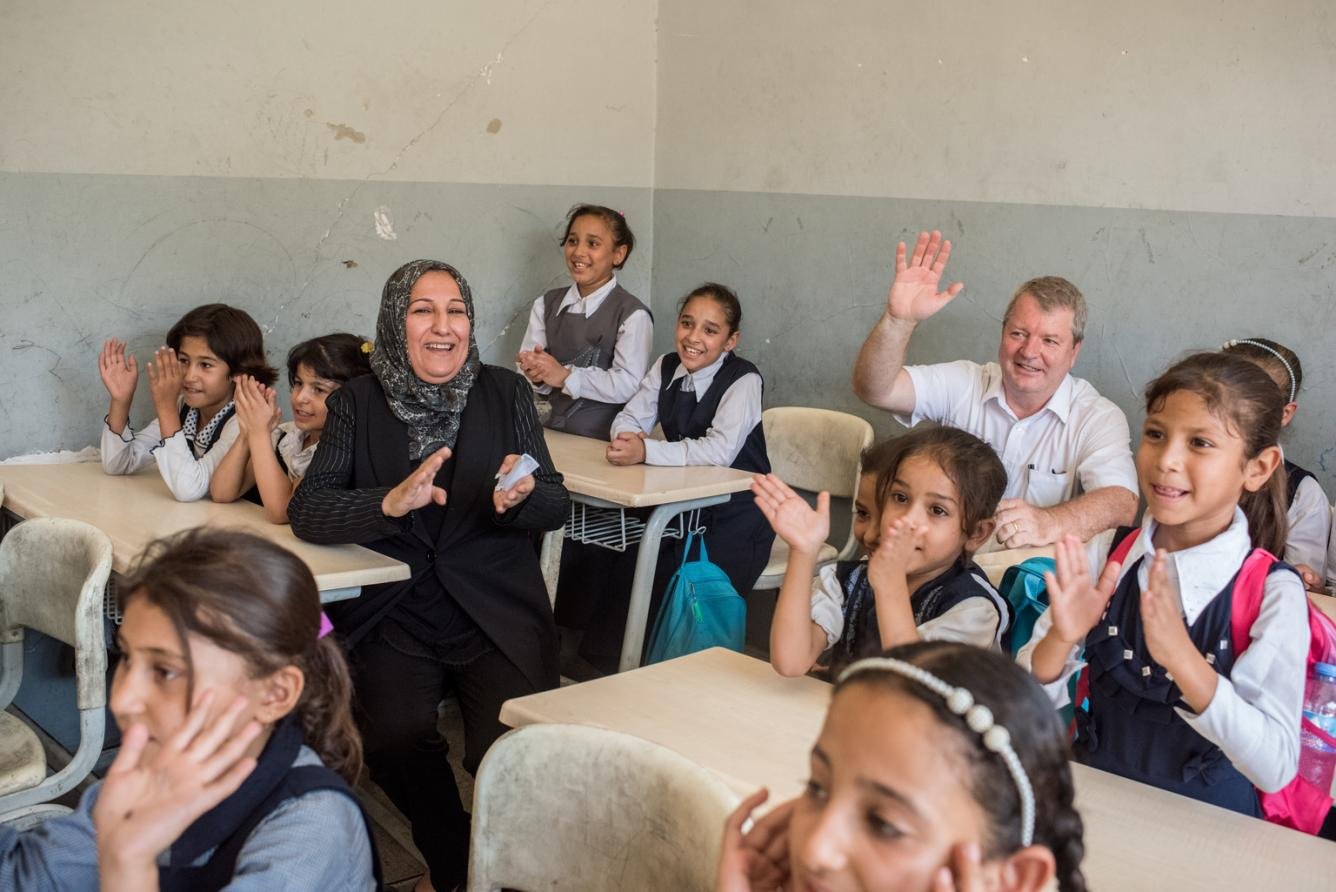 students and aid workers in a class room in iraq