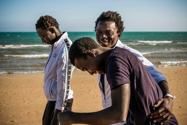 three youths laugh on a beach in Sicily