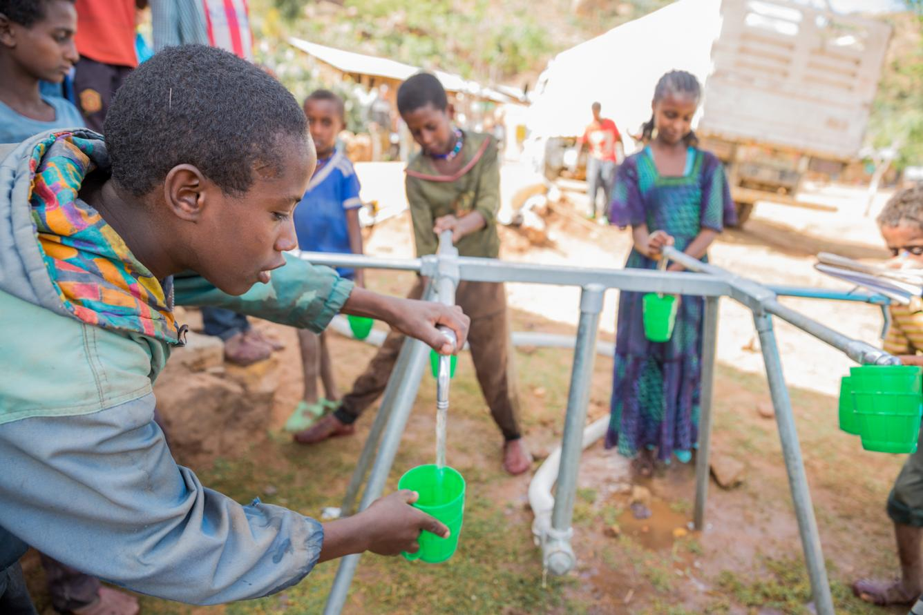 Students fill their drinking cups from a tap connected to a water bladder installed by UNICEF .