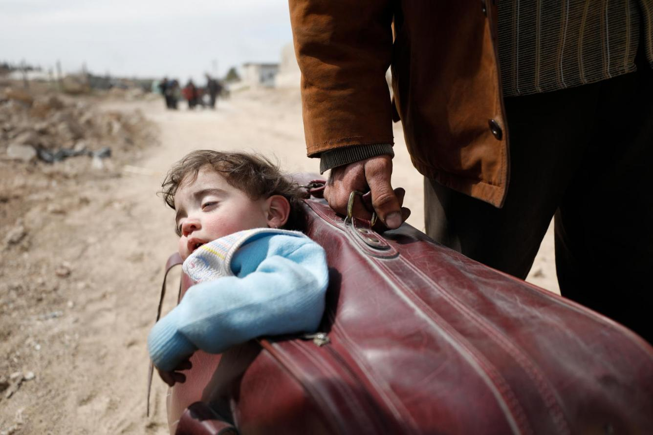 child carried in suitcase evacuating eastern Ghouta, in Syria